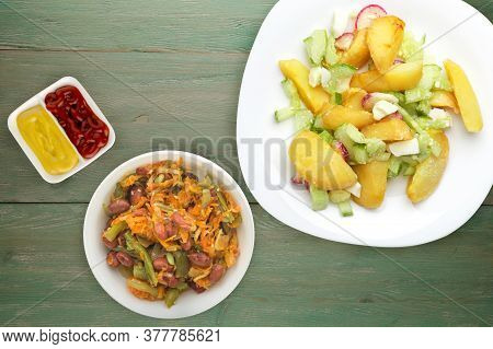 Potato Wedges With Vegetables On A White Plate On A Green Wooden Background. Unhealthy Food . Rustic
