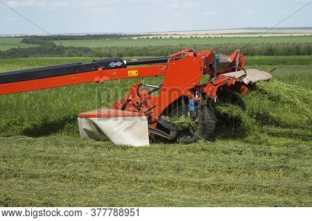 Red Tractor Trailer Cutting Grass On The Field. The Process Of Mowing Clover. Summer Work On An Agri