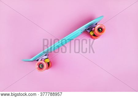 Sport Inspired Flatlay With Turquoise Penny Skateboard Isolated On Pink Background.