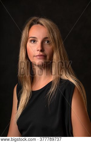 Peaceful Calm Beautiful Girl In A Black Dress On A Dark Background, Portrait Of A 30 Year Old Woman