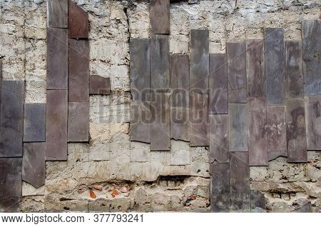 A Destroyed Wall With Narrow Vertical Brown Tiles. The Texture Of A Shabby Destroyed Brick Wall. Cit