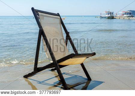 Old Chaise Longue On A Sandy Beach Against The Sea