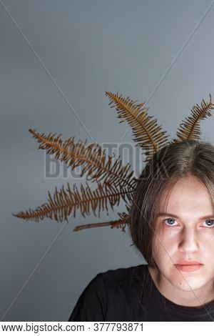Stylish Portrait Of Brunette Girl With Crown Of Fern In Her Hair, Gray Background. Stylish Hairstyle