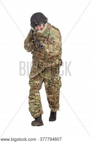 Military Commando In Uniform With A Shotgun Attacks And Aims On A White Background, Soldier In Actio