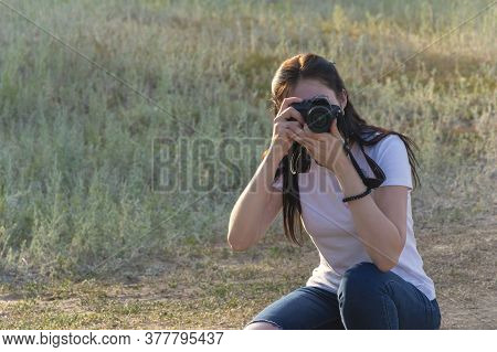 Young Woman Photographer Looks Into Her Slr Camera And Takes Pictures. A Beautiful Brunette In A Whi