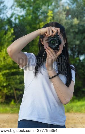 A Beautiful Brunette Holds A Slr Camera In Her Hands And Looks Into The Lens. Taking Pictures On A S