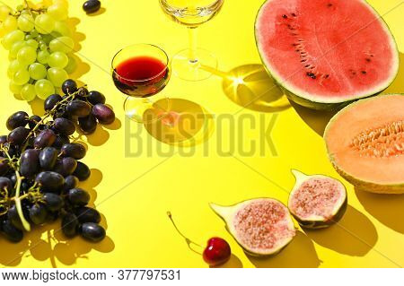 Two Glasses Of Red And White Wine. A Woman Pours Wine From A Bottle. Grapes And Other Fruits On A Ye