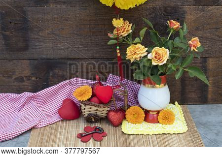 A Chinese Lantern Hangs Over The Table. There Are Yellow Roses In A Vase On The Table. Nearby Are Ca