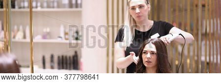 Portrait Of Coiffeur Speaking With Female Client About Hairdo. Hair Stylist Making Curls For Brunett