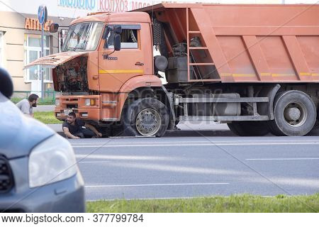 Russia, Saint-petersburg, July 2019: The Truck Has A Punctured Wheel The Driver Is Trying To Repair