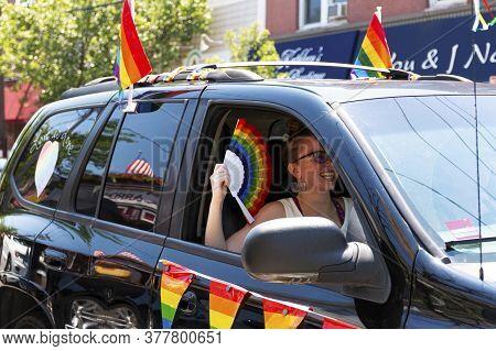 Babylon, New York, Usa - 28 June 2020: A Women Keeping Cool Using A Rainbow Colored Fan Shile Sittin