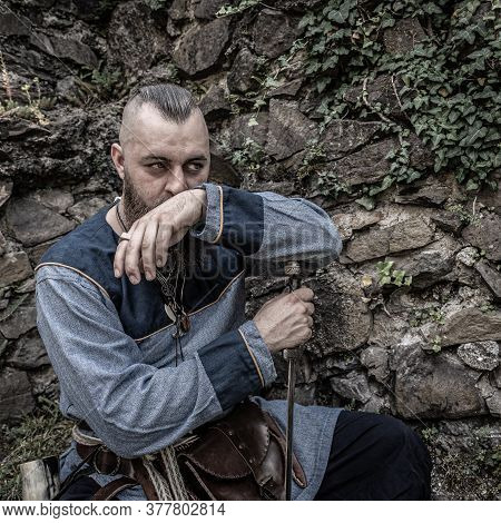 Viking Warrior With Thick Beard Sits Thoughtfully In Front Of A Stone Wall