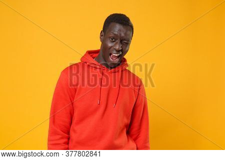 Cheerful Young African American Man Guy In Red Streetwear Hoodie Posing Isolated On Yellow Wall Back