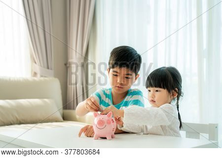 Two Asian Cute Brother And Sister Insert Coin  In Piggy Bank Together On The Table In Living Room At
