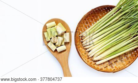Lemongrass slices on wooden spoon with  fresh lemongrass in wooden bamboo threshing basket on white background. Copy space