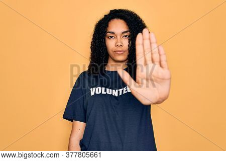 Young african american curly woman doing volunteering wearing volunteer t-shirt with open hand doing stop sign with serious and confident expression, defense gesture