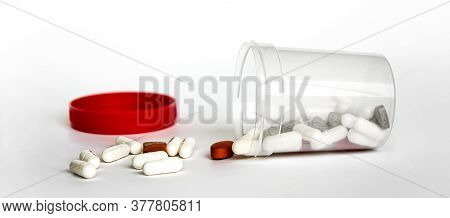 Overturned Bottle With Colored Pills Isolated On White Background. Pills Spilling Out Of Transparent