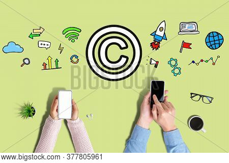 Copyright Protection Concept With Sign. Hand Holds A Smartphone On A Green Background