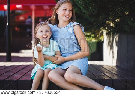 Older Sister Tickles Younger Sister On The Veranda