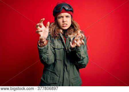 Young blonde girl wearing ski glasses and winter coat for ski weather over red background Shouting frustrated with rage, hands trying to strangle, yelling mad