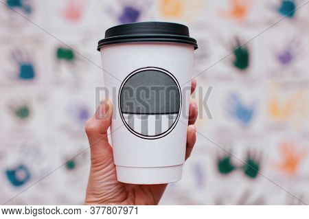 Female's Hand Holding A Plastic Cup With A Drink On A Colored Blurred Background