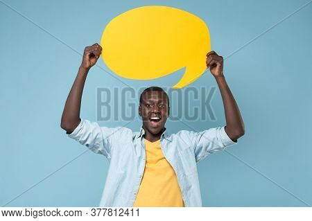 Excited Young African American Man Guy In Casual Shirt Yellow T-shirt Isolated On Blue Background In