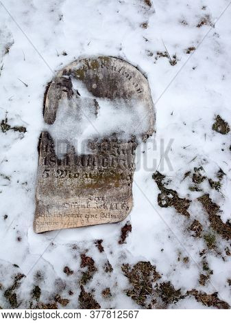Old Cemetery Gravestones With Snow On Cold Winter Day