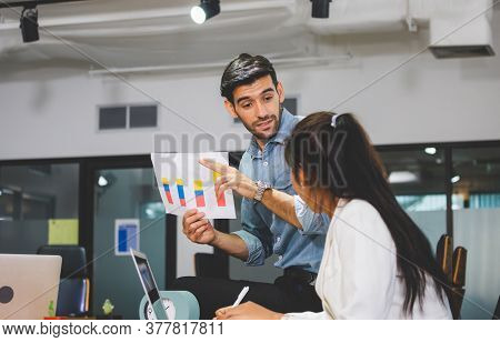 Young Business Team Of Coworkers Meeting In Creative Office, Businessman Holding Paper And Sitting O