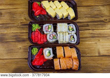 Set Of Sushi Rolls In Plastic Boxes On Wooden Table. Top View. Sushi For Take Away Or Delivery Of Su