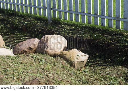 Massive Stones Abandoned On The Ground Under A Fence