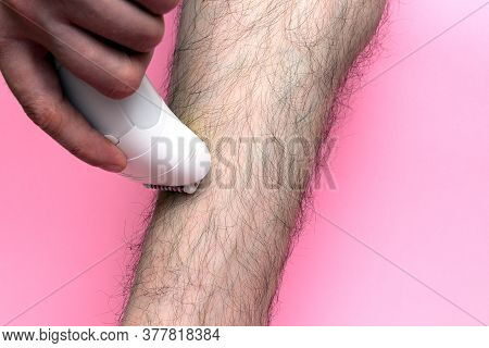 Man Epilates His Leg With An Electric Epilator Device. Close-up Male Leg Shaver Shaving. Skin Care A