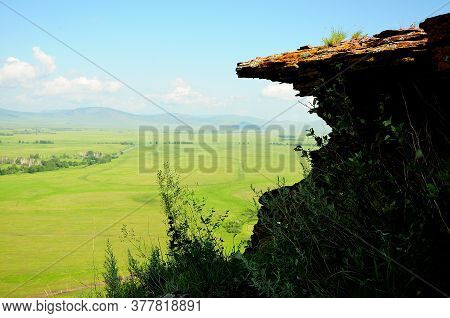 A Steep Stone Cliff Overhanging An Abyss Against The Backdrop Of A Picturesque Valley.