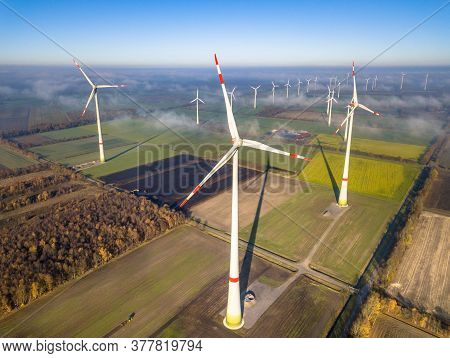 Aerial View Of Wind Energy Turbines On Windfarm Above Mist Layer On German Countryside In The Mornin