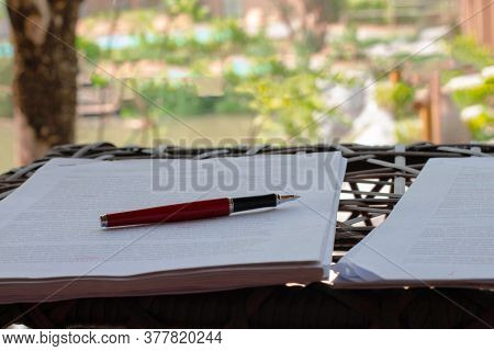 Red Pen On Pile Of Blurred Paperwork On Table