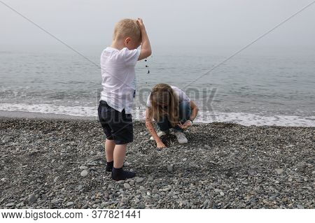 A Little Boy With Blond Hair And A Girl Playing With Pebbles On The Beach.travelling To The Seaside