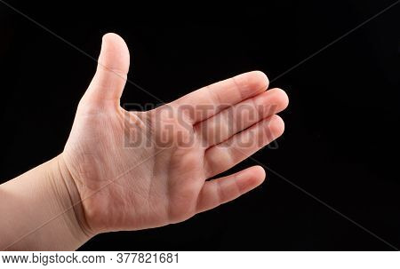 Hand Tearing A Heart Shaped Aluminium Foil On A Wooden Background