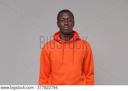 Serious Young African American Man Guy In Orange Streetwear Hoodie Posing Isolated On Grey Backgroun