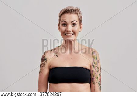Portrait Of Half Naked Tattooed Woman With Short Hair Frowning Face, Feeling Awkward, Silly Isolated
