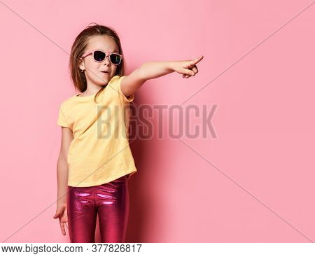Surprised Amazed Frolic 6-7 Y.o. Kid Girl In Yellow T-shirt, Shiny Glossy Pink Leggings And Sunglass