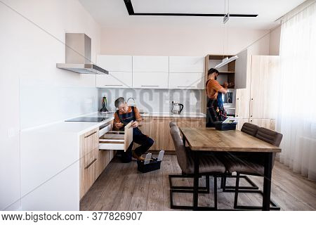 Two Handymen, Workers In Uniform Assembling Kitchen Cupboard, Cabinet Using Screwdriver Indoors. Fur