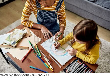 Caucasian Little Girl Spending Time With African American Baby Sitter. They Are Drawing A Mouse Toge
