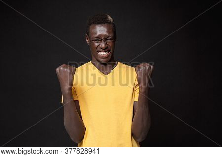 Joyful Young African American Man Guy In Yellow T-shirt Posing Isolated On Black Wall Background Stu