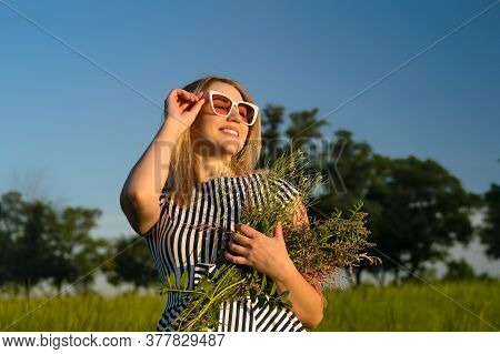 Woman In Striped Sundress And Sunglasses On The Field. Eco-friendly Girl In Beautiful Dress On A Fie