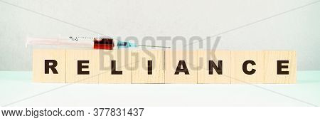 Small Wooden Cubes With Word Reliance And Syringe With Red Liquid On Light Green Table Close View