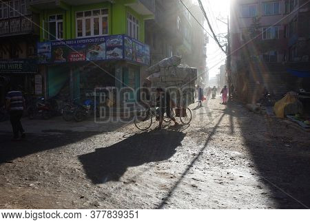 Kathmandu, Nepal - June 20, 2019: Cargo bicycle delivery fully loaded rickshaw on narrow street in old town with opposite sun and long shade, Local daily life