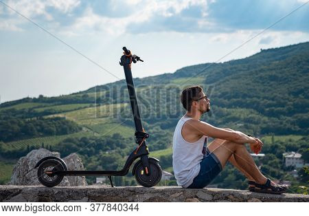 Young Man Riding An Electric Scooter On Mountain Range. Ecological Transportation Concept