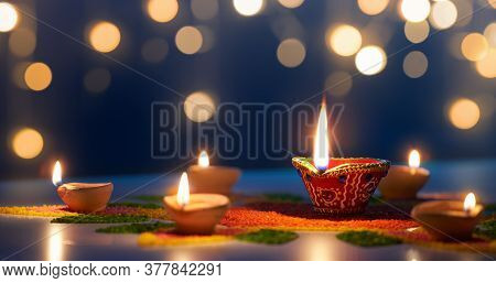 Happy Diwali, Diya Lamps Lit On Colorful Rangoli With Bokeh Light Background