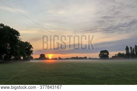 Dramatic And Colorful Sunrise Sky. Dramatic And Colorful Sunrise Or Sunset Sky Over A Grassy Green F
