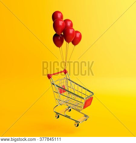 Flying Shopping Cart With Balloons On A Yellow Background. Shopping Trolley. Grocery Push Cart. Mini