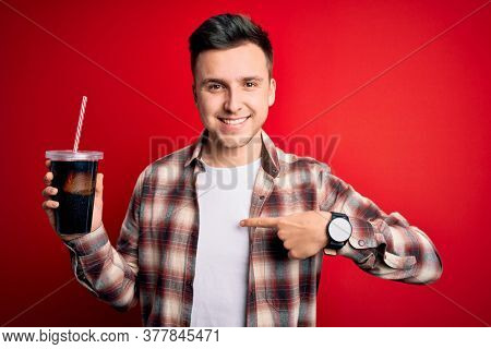 Young handsome caucasian man drinking a fresh soda refreshment over red background with surprise face pointing finger to himself